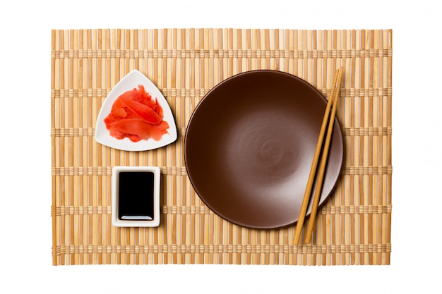 Empty round brown plate with chopsticks for sushi, ginger and soy sauce on yellow bamboo mat background. top view with copyspace