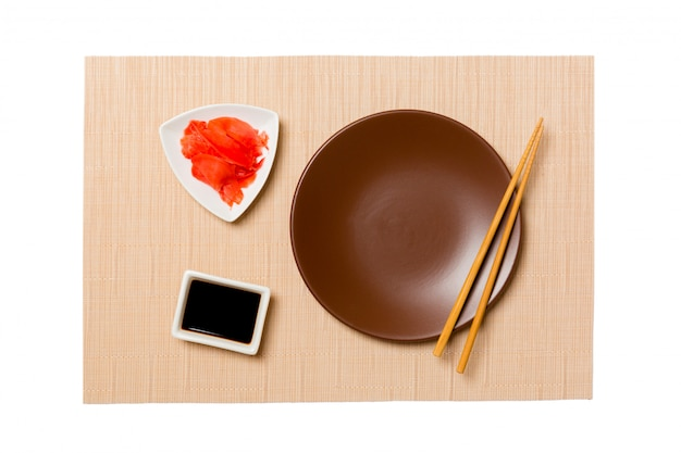 Empty round brown plate with chopsticks for sushi and soy sauce, ginger on brown sushi mat .