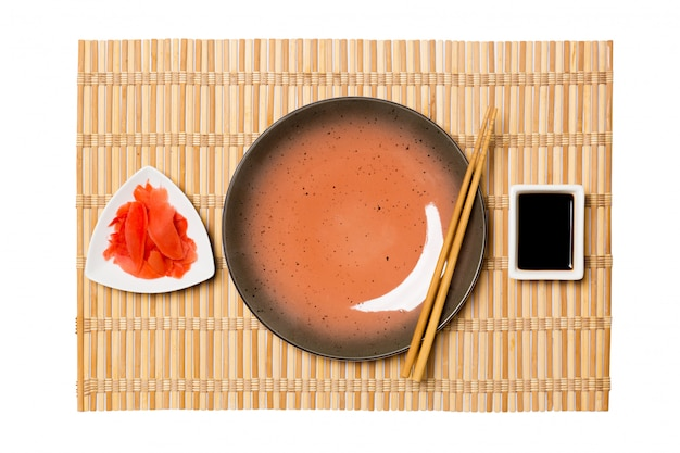 Empty round brown plate with chopsticks for sushi and soy sauce, ginger on yellow bamboo mat . top view with  copyspace