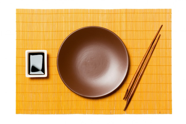 Empty round brown plate with chopsticks for sushi and soy sauce on yellow bamboo mat