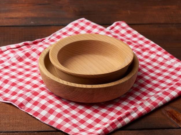 Пустая круглая коричневая деревянная тарелка стоит на коричневом столе