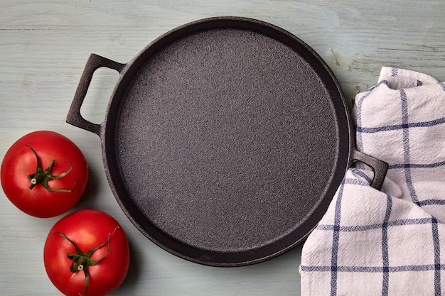 Empty round cast iron pan tea towel and tomatoes