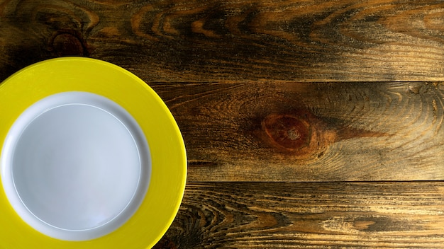 Пустая круглая керамическая тарелка с желтым краем на грубой деревянной поверхности