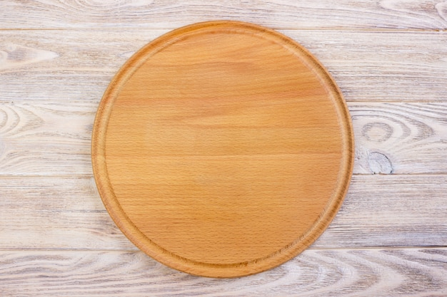Empty round cutting board on a wooden table