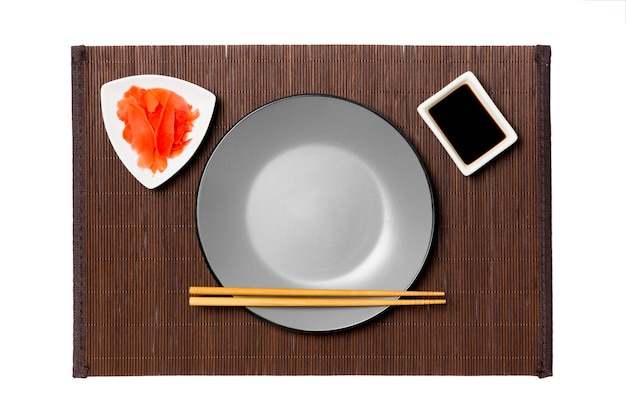 Empty round gray plate with chopsticks for sushi, ginger and soy sauce on dark bamboo mat surface