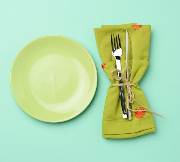 Пустая круглая зеленая керамическая тарелка и металлическая вилка и нож, зеленый фон, вид сверху