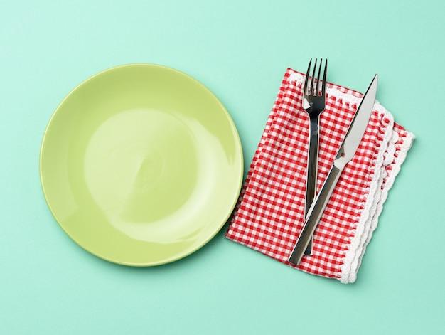 空の丸い緑色のセラミックプレートと金属のフォークとナイフ
