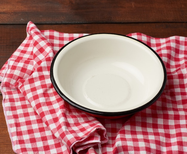 Пустая круглая металлическая белая тарелка стоит на деревянном коричневом столе