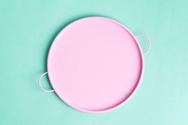 明るい青緑色の背景に焼きたての食品を表すための空の丸いピンクセラミックプレート。