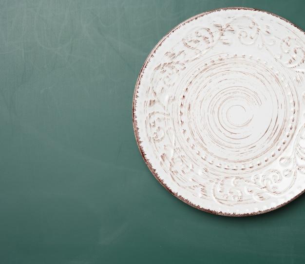 Пустая круглая тарелка для основных блюд на зеленом столе, вид сверху
