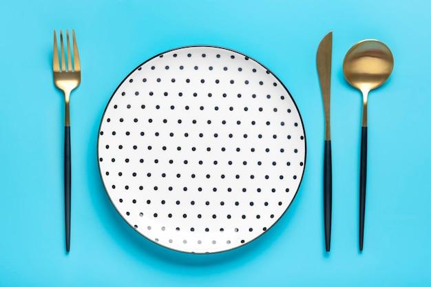 파란색 테이블에 빈 원형 접시 포크 나이프 상위 뷰 아침 점심 또는 저녁 식사를 위한 평평한 접시