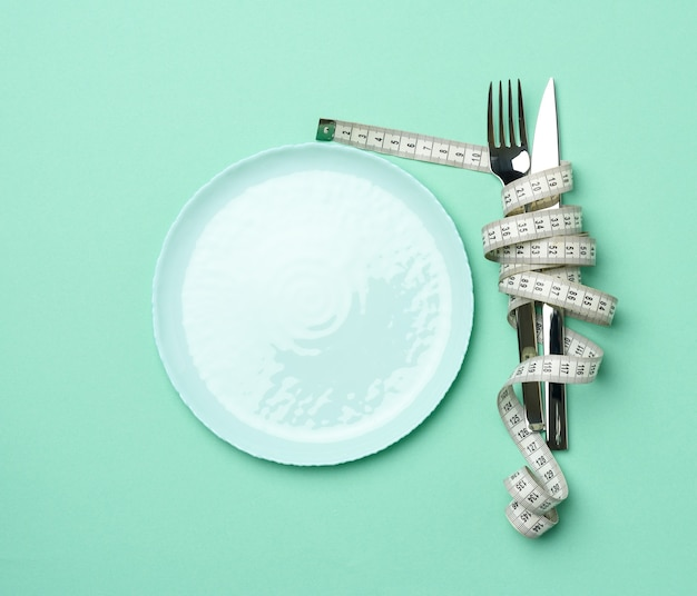 Empty round plate and fork and knife wrapped in white measuring tape on blue background, weight loss concept, flat lay