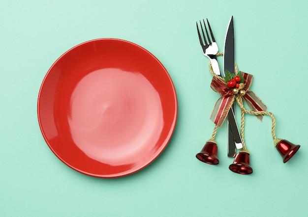 Пустая круглая красная керамическая тарелка, нож и вилка на зеленом фоне, праздничная сервировка стола на рождество и новый год, вид сверху