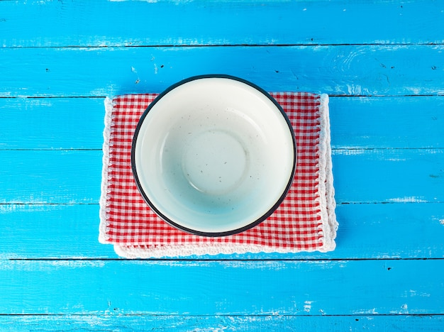 Empty round white metal plate on a red white textile napkin