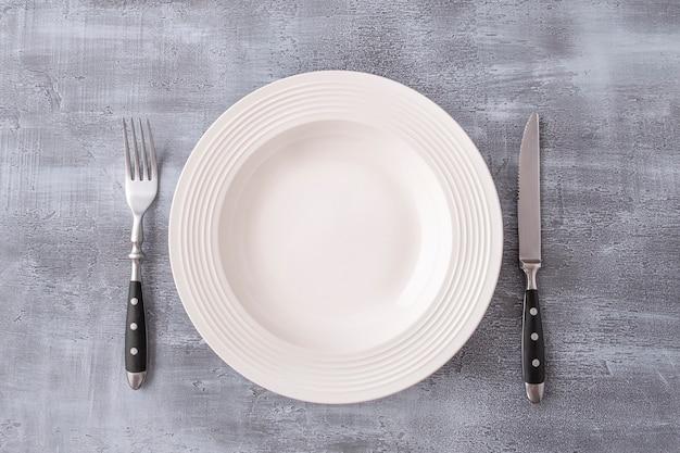 空の白い丸皿にフォークとナイフを添えてください。上面図。コピースペース