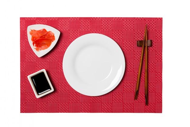 Пустая круглая белая тарелка с палочками для суши и соевым соусом