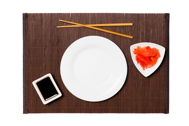 Пустая круглая белая тарелка с палочками для суши, имбиря и соевого соуса на темном фоне бамбуковой циновки. вид сверху с копией пространства для вашего дизайна.