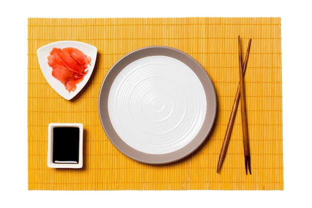 Empty round white plate with chopsticks for sushi, ginger and soy sauce on yellow bamboo mat background. top view with copy space for you design.