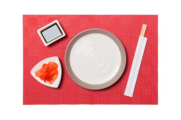 Empty round white plate with chopsticks for sushi and soy sauce, ginger on red mat sushi. top view