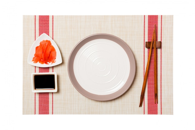 Empty round white plate with chopsticks for sushi and soy sauce, ginger on sushi mat background