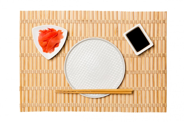 Empty round white plate with chopsticks for sushi and soy sauce, ginger on yellow bamboo mat background