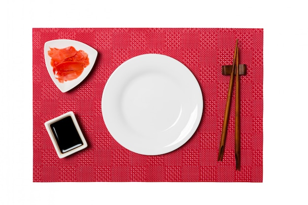 Empty round white plate with chopsticks for sushi and soy sauce