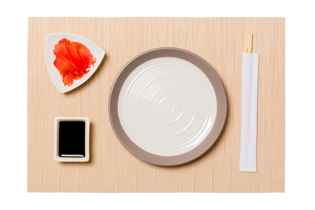 Empty round white plate with chopsticks for sushi