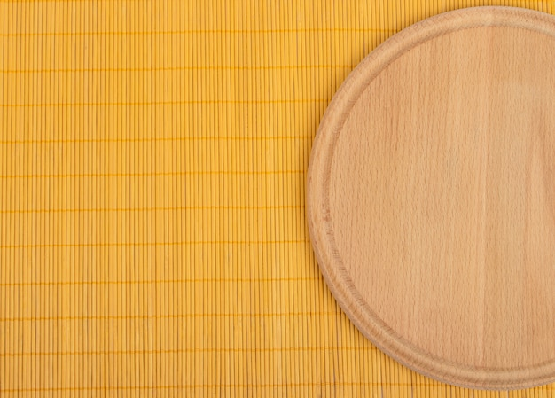 Empty round wooden board with tablecloth background