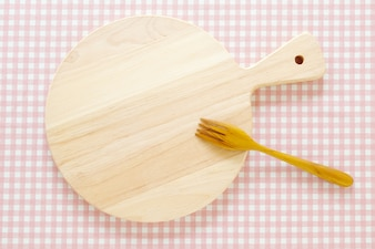 Empty round wooden chopping board and fork on pink tablecloth