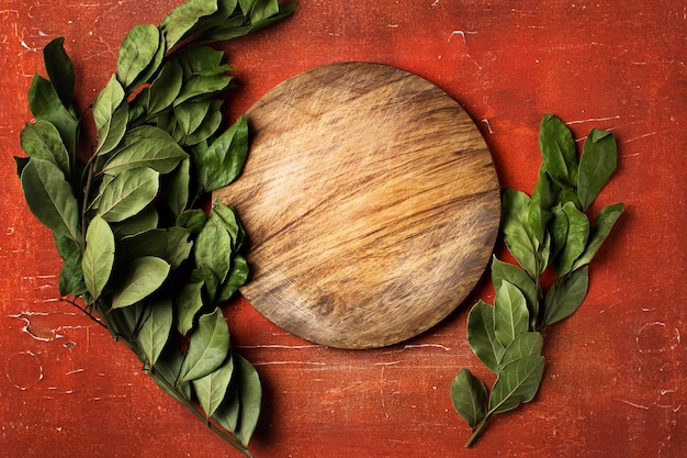 Empty round wooden cutting board on red background with bay laurel leaves, food backgrounds