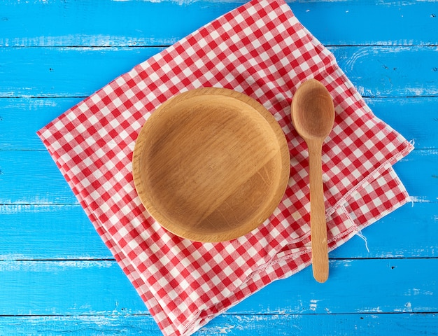Empty round wooden plate and spoon on a red white textile napkin