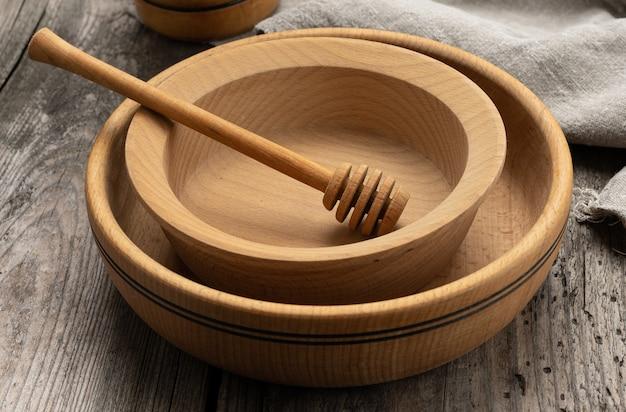 Пустые круглые деревянные тарелки и ложки на сером столе, медовая палочка, крупным планом