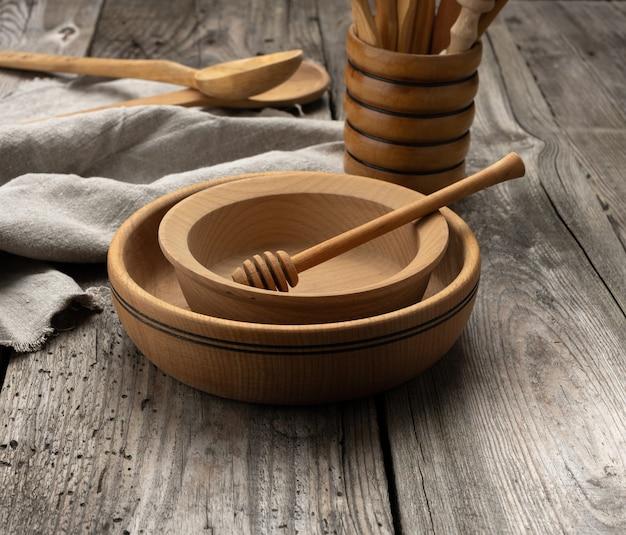 Пустые круглые деревянные тарелки и ложки на сером столе, медовая палочка