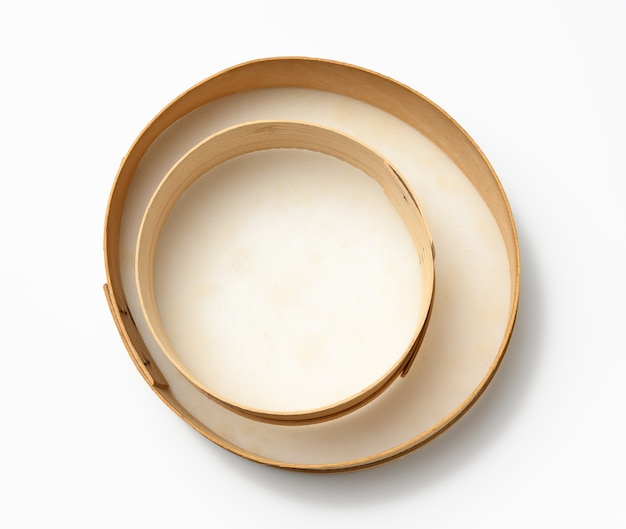 Empty round wooden sieve for sifting flour on white background, top view