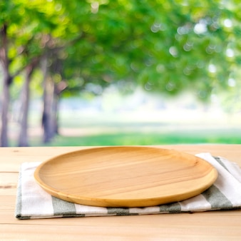 Empty round wooden tray and napery on table over blur tree background, for food and product display montage, template