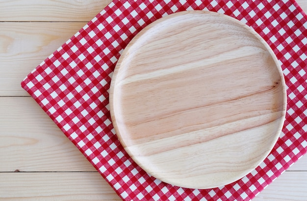 Empty round wooden tray on red white tablecloth which covering wood table background