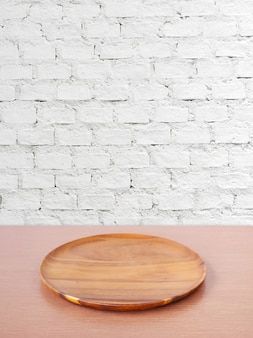 Empty round wooden tray on table over white brick wall background