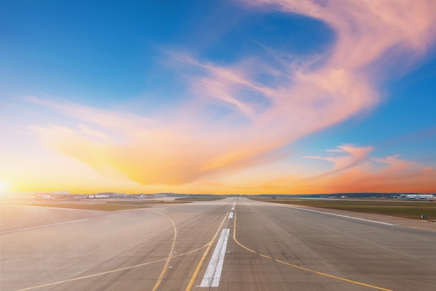 Empty runway at evening airport during sunset