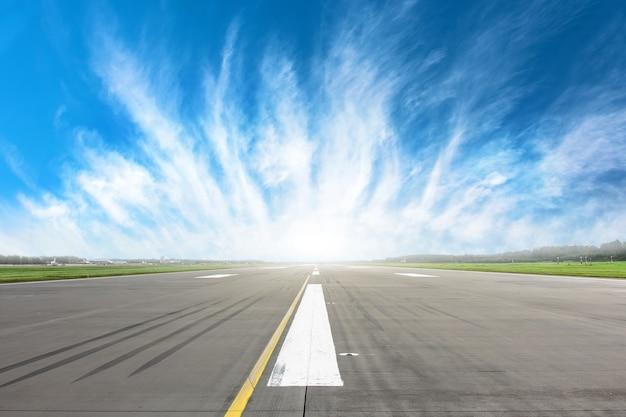 地平線上に美しい雲のマーキングが付いた空の滑走路ストリップ。