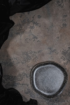 Empty rustic black plate on brown