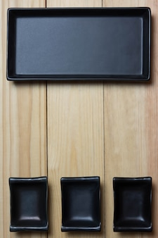 Empty rustic black plate over wooden table. aerial view, with copy space.