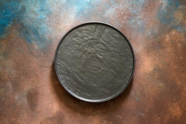 Empty rustic black stone plate on dark concrete