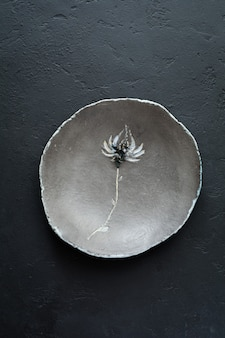 Empty rustic flat plate of gray clay with beautiful flower on black concrete table. selective focus. top view. copy space.