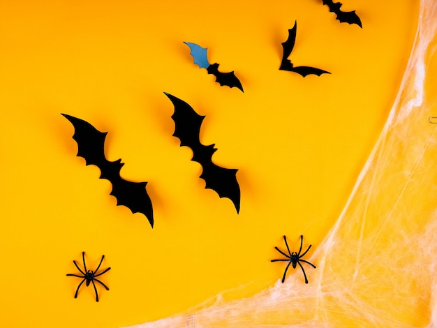Empty rustic table in front of spider web background, orange background with bats and cobwebs, halloween
