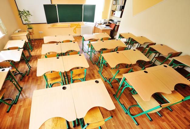Пустые школьные парты стулья на зеленой доске концепция возвращения в школу без образования людей