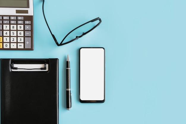 空の画面スマートフォンとコピースペースのあるビジネスデスクオフィスのファイルフォルダ