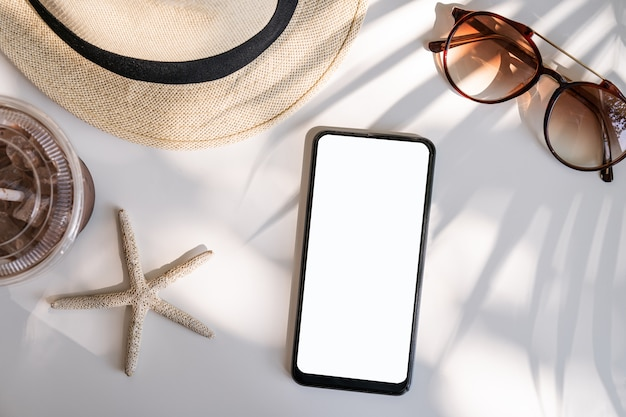 Empty screen smart phone with travel accessories on the table, summer vacation concept