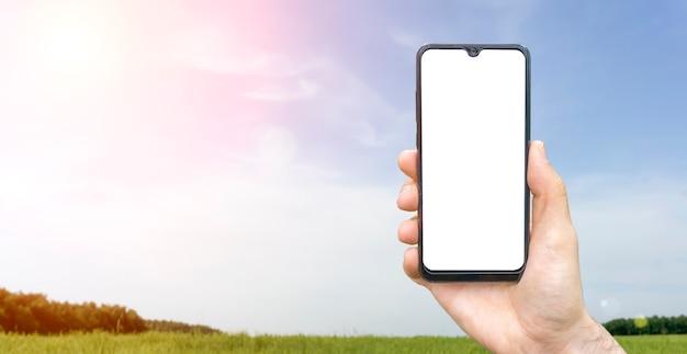Пустой экран смартфона фон. рука с пустым смартфоном на фоне летнего солнечного спокойного пейзажа с деревенским лугом, лесом и небом. фото высокого качества