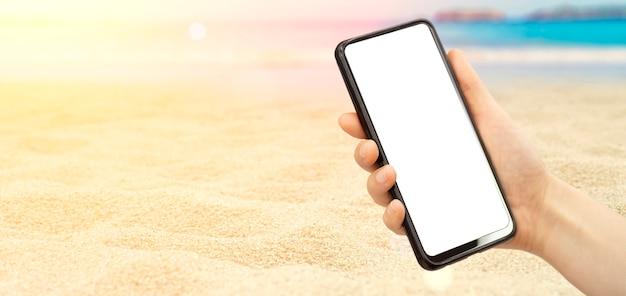 夏の日当たりの良い背景の手に空の画面のスマートフォン。