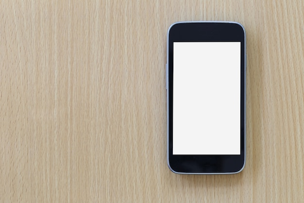 Empty screen of smartphone placed on a brown wooden floor.